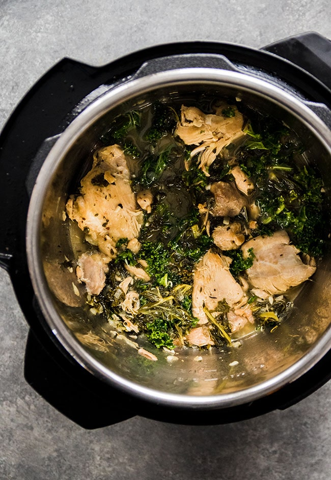 Overhead photo of lemon chicken thighs and kale in an Instant Pot