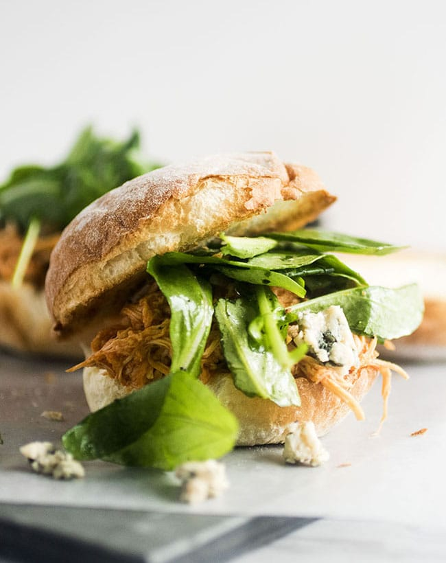 Shredded chicken, arugula, and buffalo sauce stacked on a slider roll in front of a white background with crumbled blue cheese in the foreground