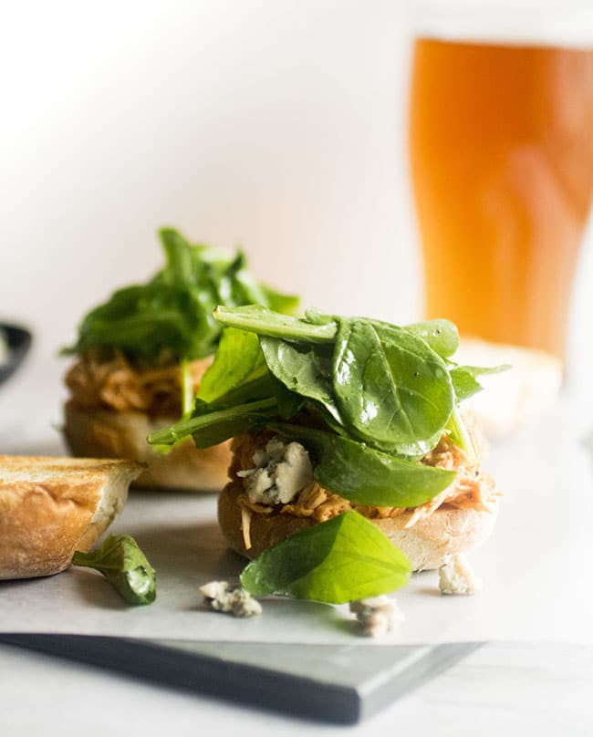 Slider roll topped with chicken, blue cheese, and arugula in front of a white background