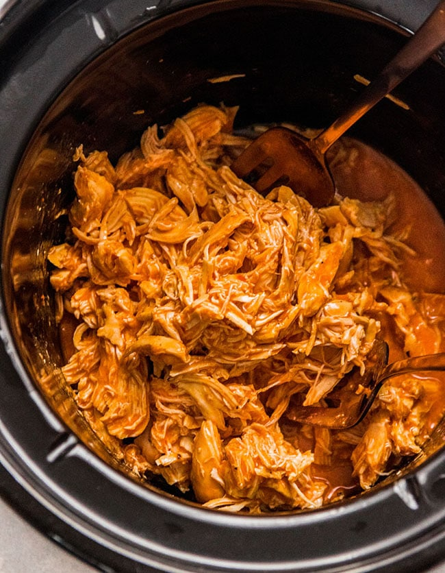 Two forks shredding buffalo chicken in a black slow cooker
