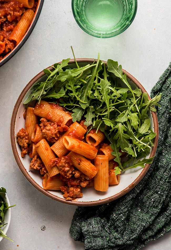 Overhead photo of rigatoni with tomato sauce next to arugula salad on a white ceramic plate next to a green glass of water