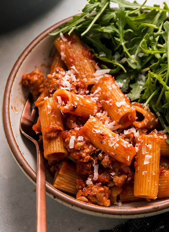 rigatoni with tomato sauce and arugula salad on a white plate with a copper fork