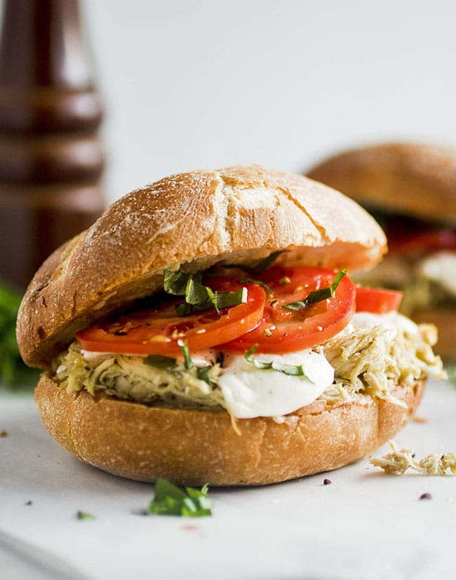 Sandwich roll with shredded chicken and tomato slices in front of a white background.