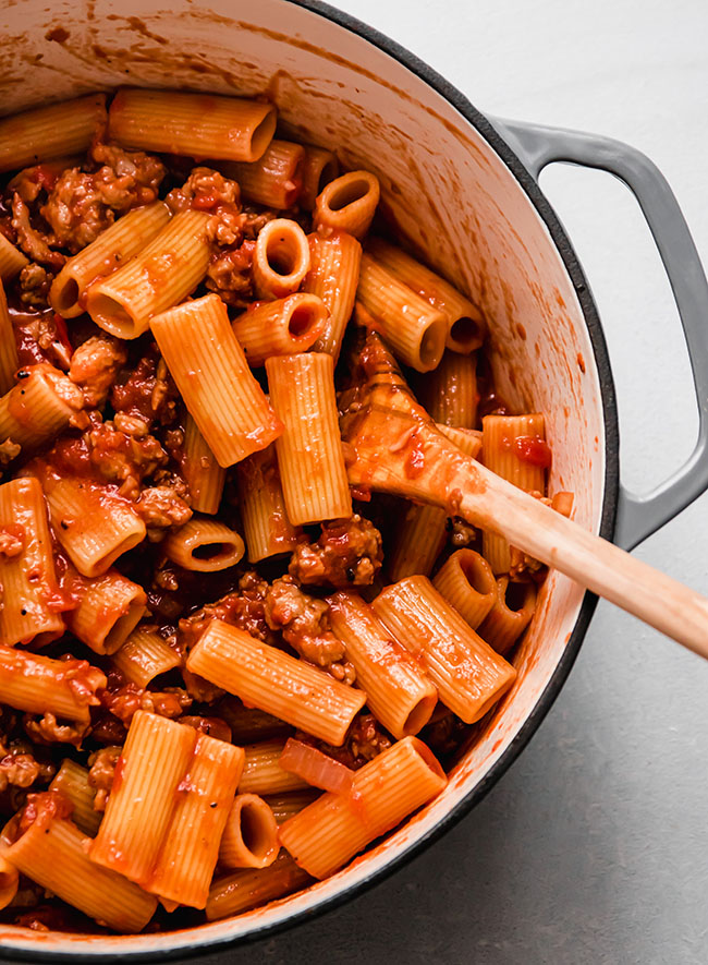 Wooden spoon stirring rigatoni with tomato sauce in a grey dutch oven