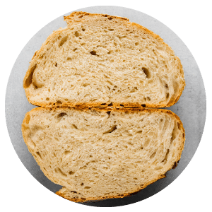 two halves of a loaf of bread on a white surface