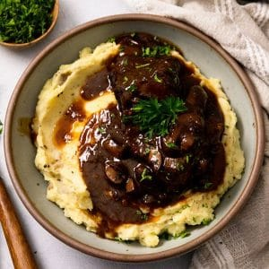 Overhead photo of a grey bowl filled with mashed potatoes and short ribs with red wine sauce