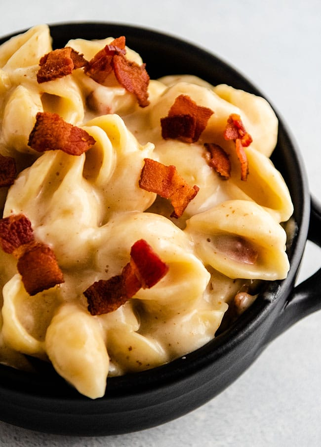 Mac and cheese with shell pasta topped with crispy bacon in a black baking dish on a white background