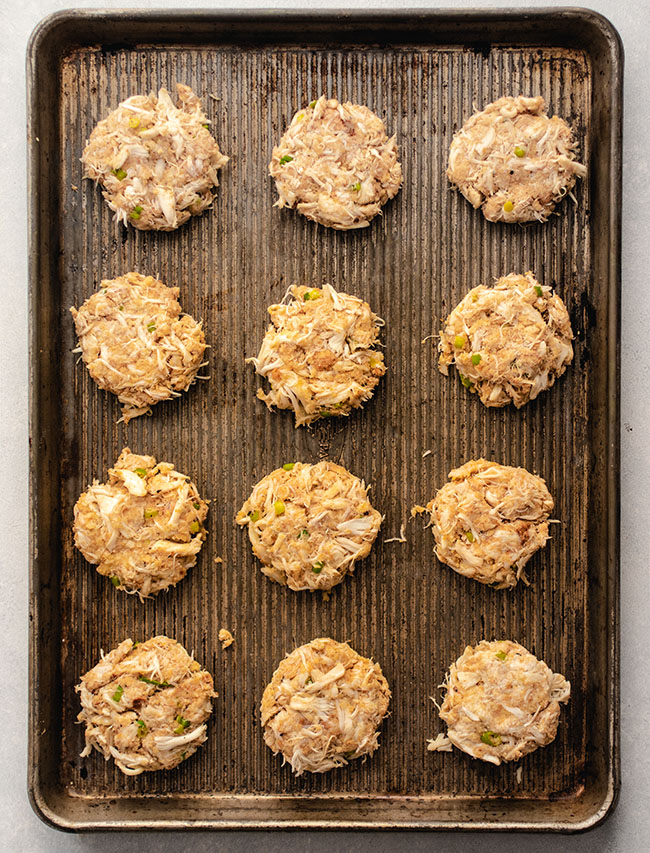 Overhead photo of twelve raw crab cakes on a large baking sheet