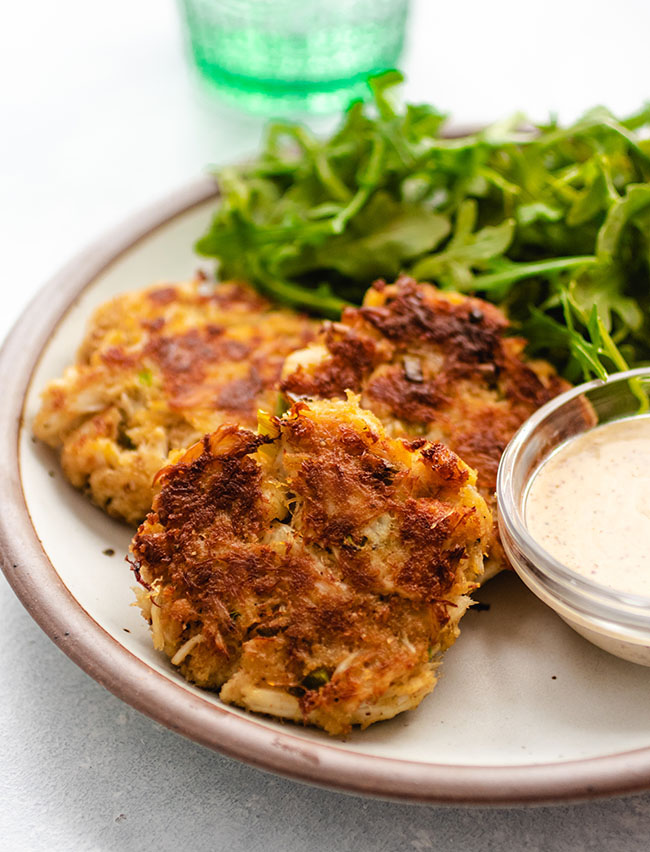 Three crab cakes on a white plate next to a bowl of aioli