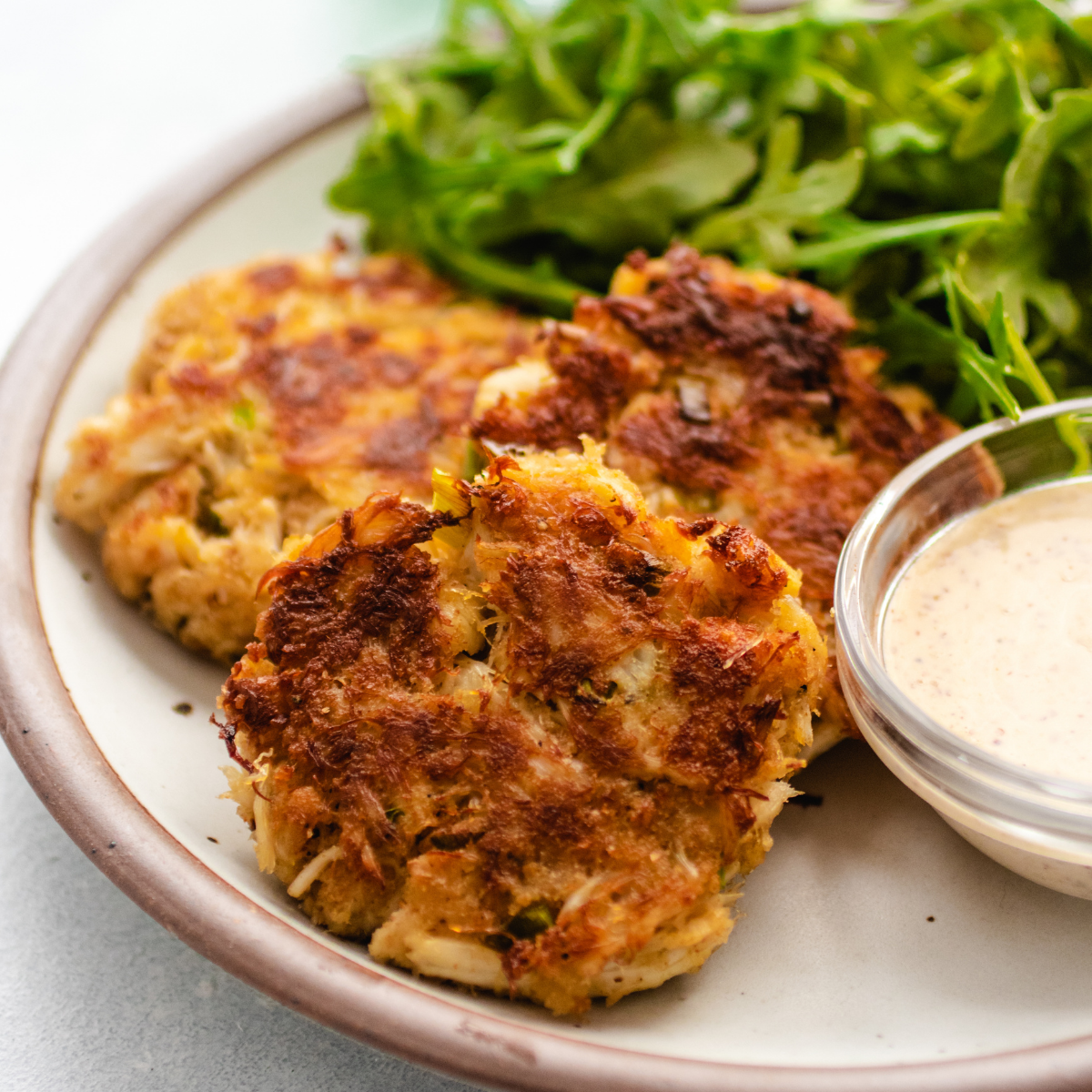 Three crab cakes on a white plate next to a small bowl of aioli.