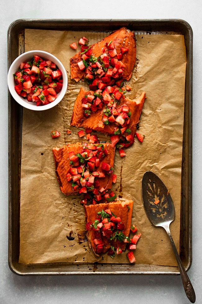 Overhead photo of four salmon pieces topped with strawberry salsa on a baking sheet lined with brown parchment paper