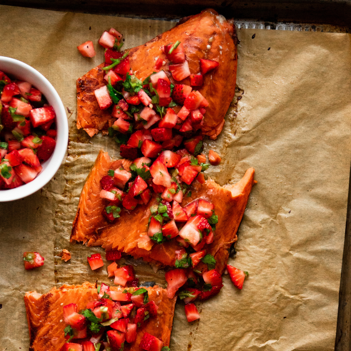 Salmon fillet topped with strawberry salsa on a baking sheet lined with brown parchment paper.