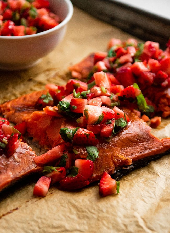 Salmon fillet topped with strawberry salsa on a piece of brown parchment paper
