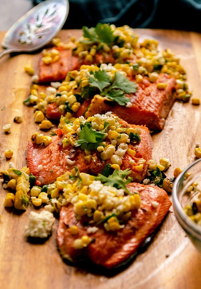 A fillet of grilled salmon, sliced into portions and topped with corn salsa.
