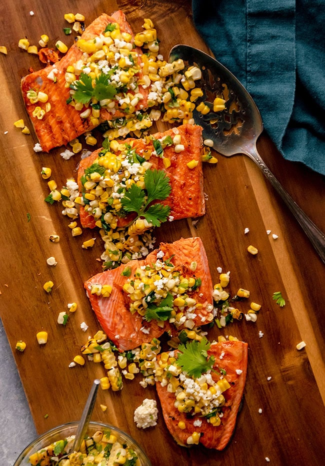 A sockeye salmon fillet on a wooden cutting board, topped with grilled corn salsa and fresh cilantro.