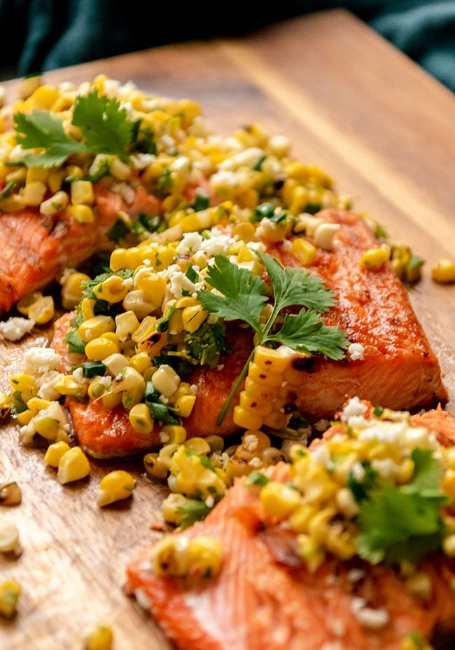 Grilled sockeye salmon portion topped with grilled corn salsa and fresh cilantro on a wood surface.