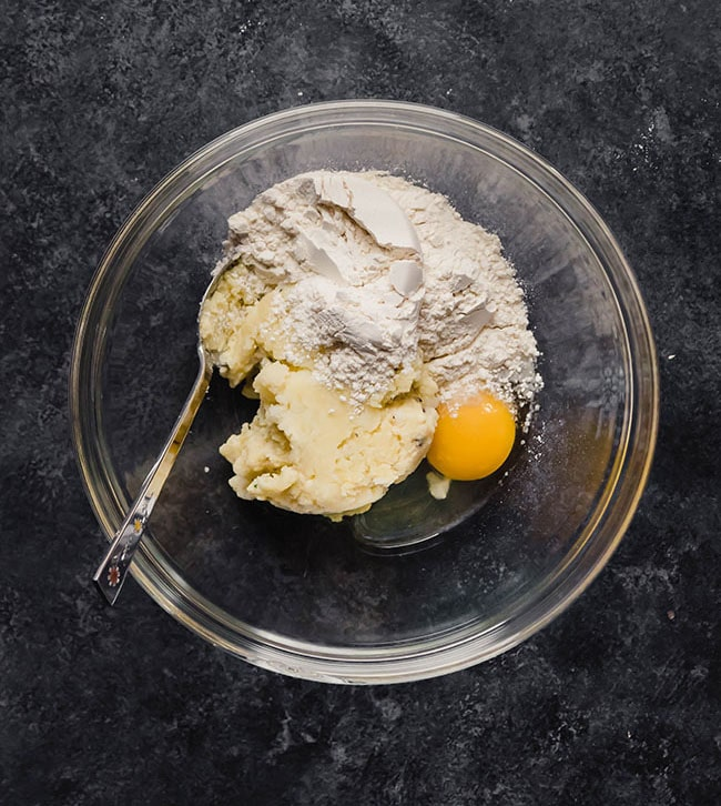 Mashed potatoes, flour, and an egg in a glass bowl on a black countertop.