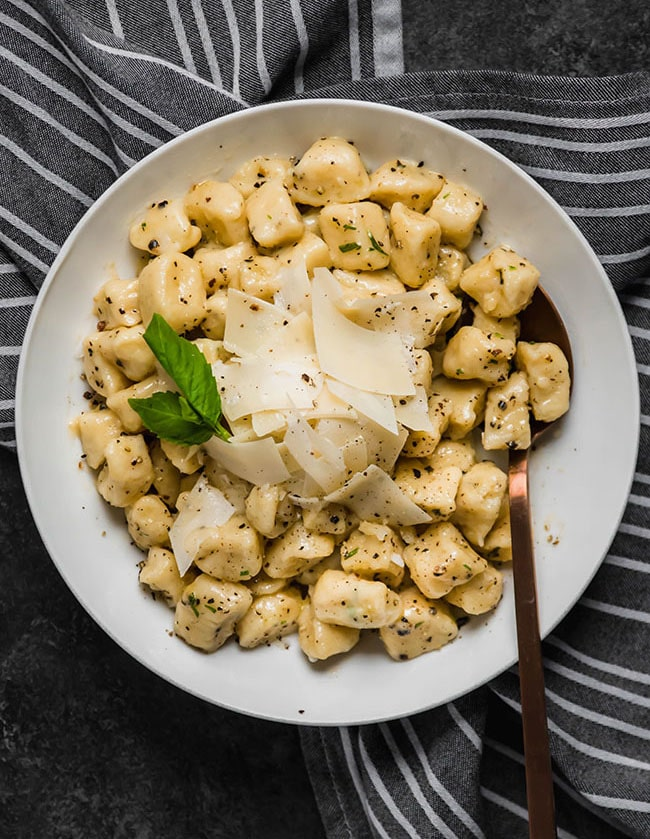 Potato gnocchi in a white bowl atop a striped napkin, topped with parmesan cheese and fresh basil.