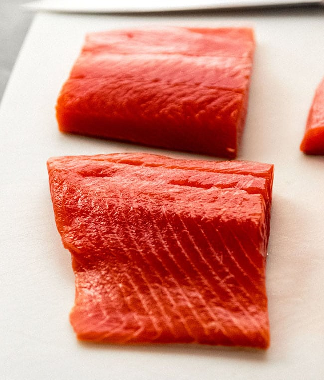 Two portions of sockeye salmon on a white cutting board.