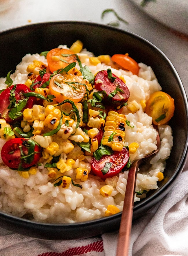 Risotto topped with halved cherry tomatoes, grilled corn, and fresh basil in a black bowl with a copper fork