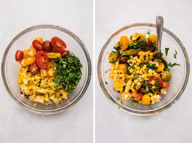 Overhead photo of halved cherry tomatoes, grilled corn kernels, and sliced basil being stirred together in a glass bowl