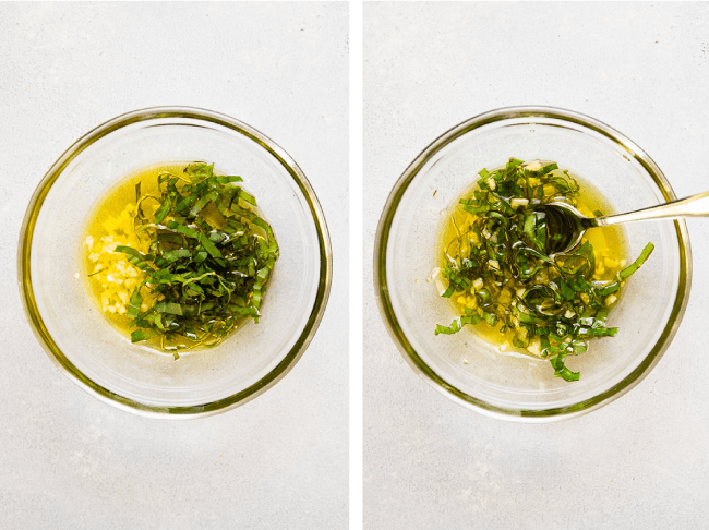 Spoon mixing basil, chopped garlic, and olive oil together in a glass bowl.