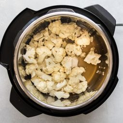 Cauliflower florets and vegetable stock in the bowl of an Instant Pot.