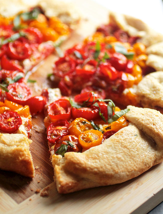 A slice of tomato galette on a wooden cutting board.