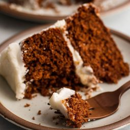 Copper fork holding a bite of a layered spice cake with white frosting.