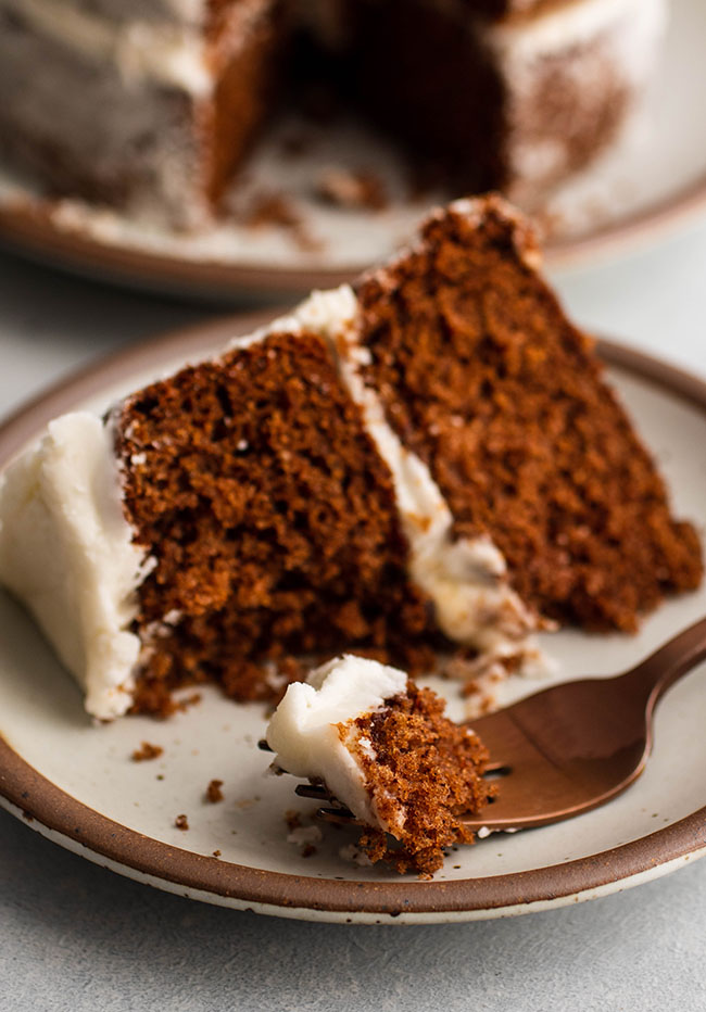 Slice of dark brown apple butter cake with white frosting on a light grey plate, with a copper fork cutting one bite off the end