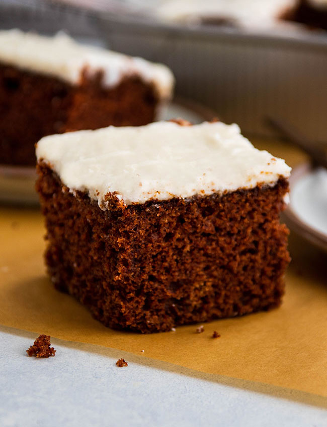 Square piece of brown cake with white frosting, sitting on a piece of brown parchment paper in front of a silver pan