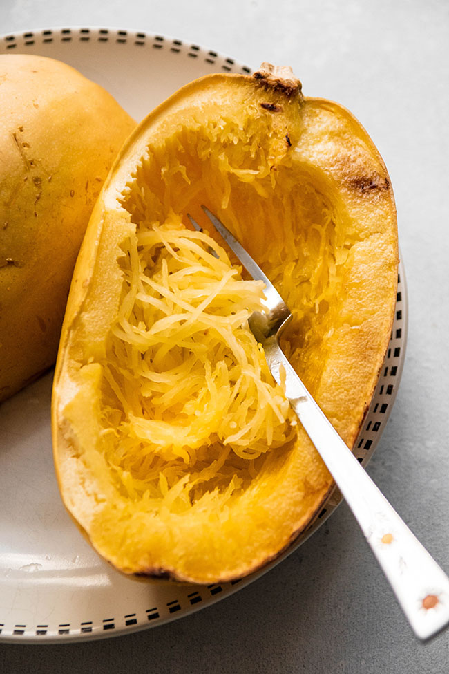 Silver fork shredding spaghetti squash into long strands