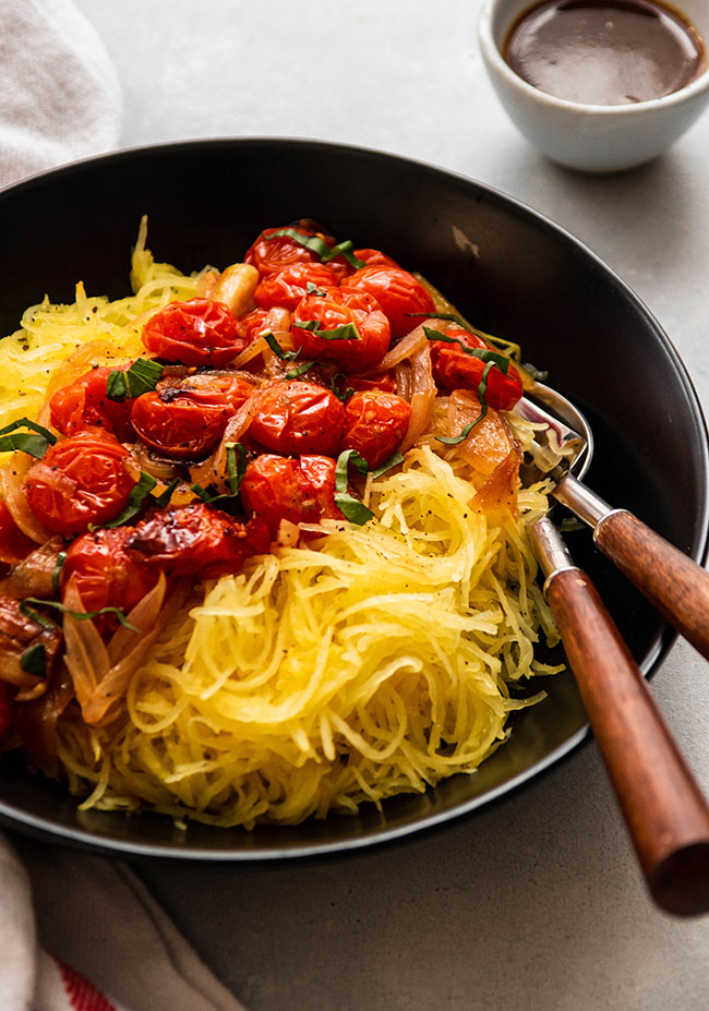 Two wooden forks sticking out of a shallow black bowl filled with shredded spaghetti squash and roasted tomatoes