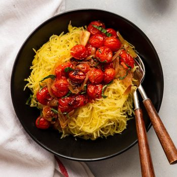 Overhead photo of a shallow black bowl filled with spaghetti squash and roasted tomatoes