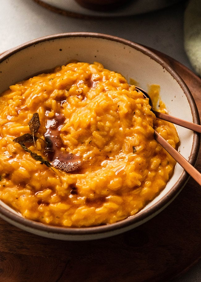 Two copper spoons tucked into a speckled white bowl filled with bright orange butternut squash risotto.