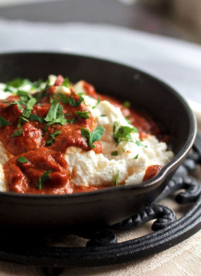 Small cast iron skillet filled with ricotta cheese and topped with a dark red pepper sauce.