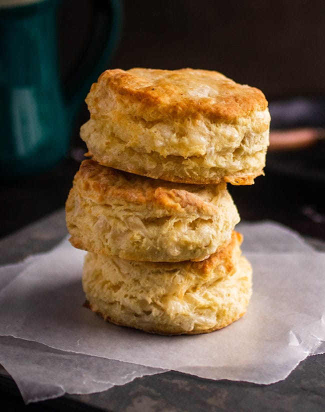 Stack of three gruyere biscuits on a piece of parchment paper in front of a green mug.