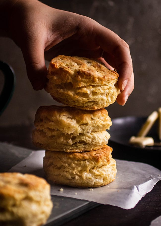 Hand adding a biscuit to a stack of biscuits on a dark background.