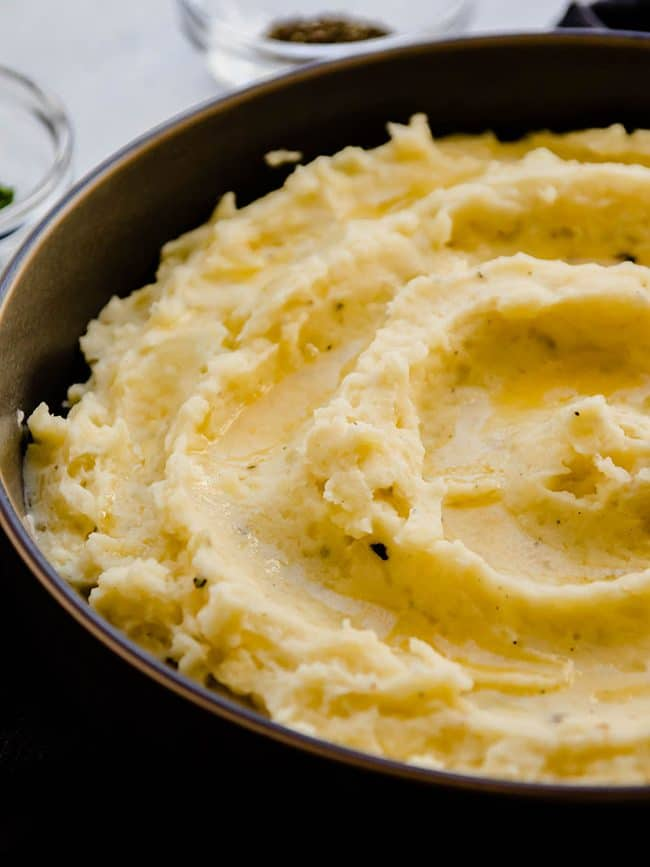 Mashed potatoes swirled into a grey bowl in front of a window and topped with melted butter.