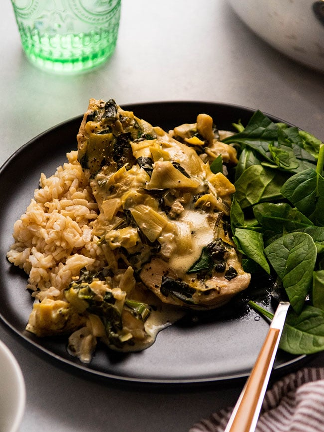 Chicken breast covered in spinach artichoke sauce on a black plate with a wooden fork