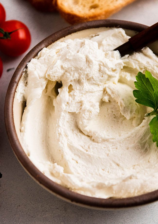Wooden spoon stirring creamy goat cheese in a small brown bowl.