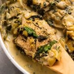 Wooden spoon lifting a chicken breast with spinach sauce out of a metal pan.