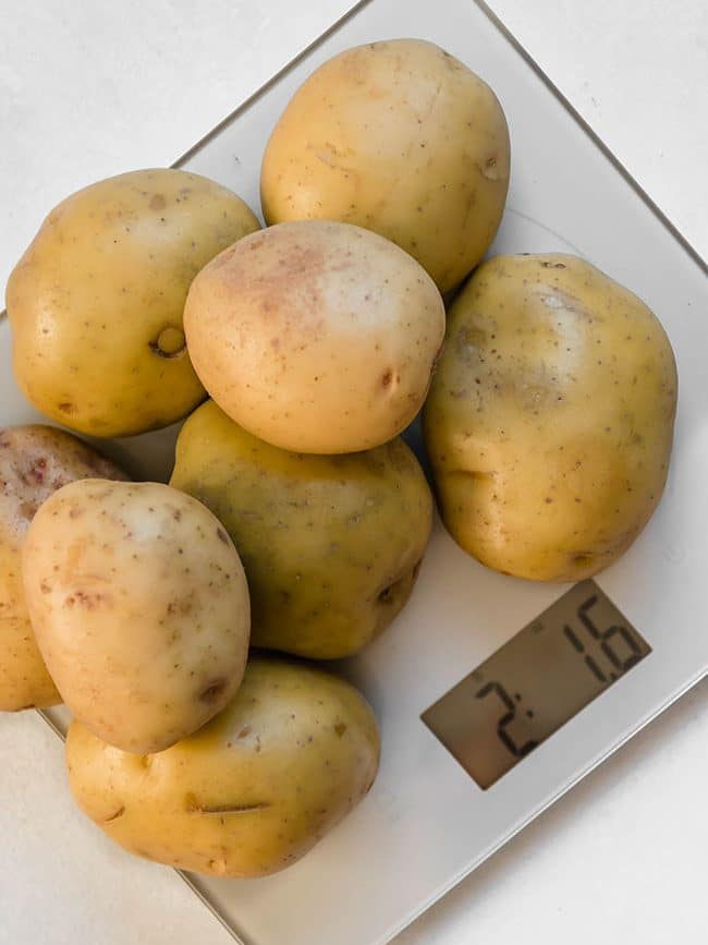 overhead photo of potatoes on a silver kitchen scale sitting on a white table