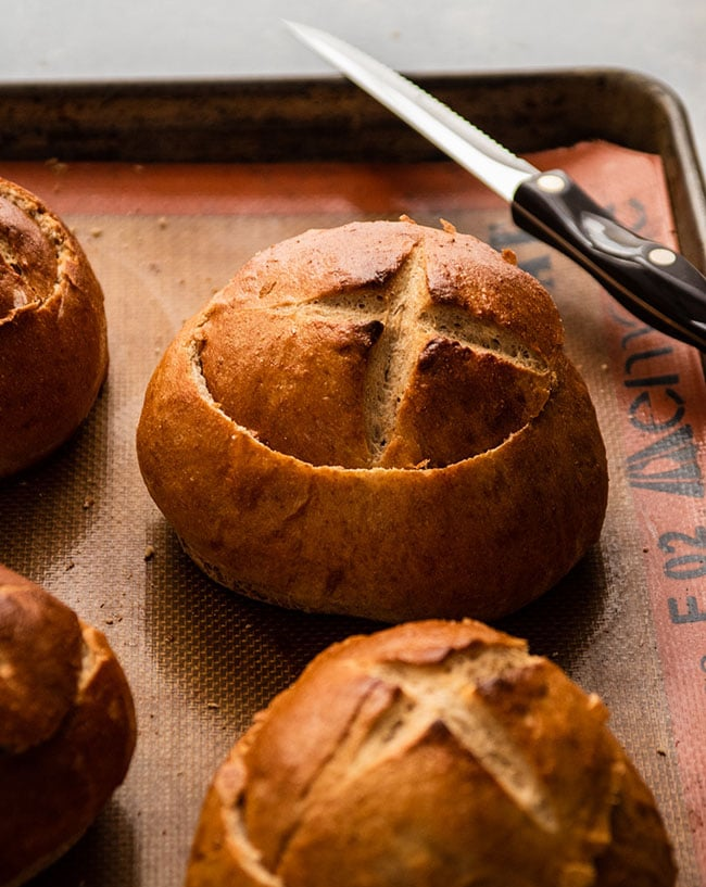 Four bread bowls with their tops cut off on a baking sheet next to a small knife.