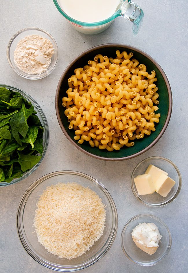 Small bowls filled with mac and cheese ingredients on a white surface.