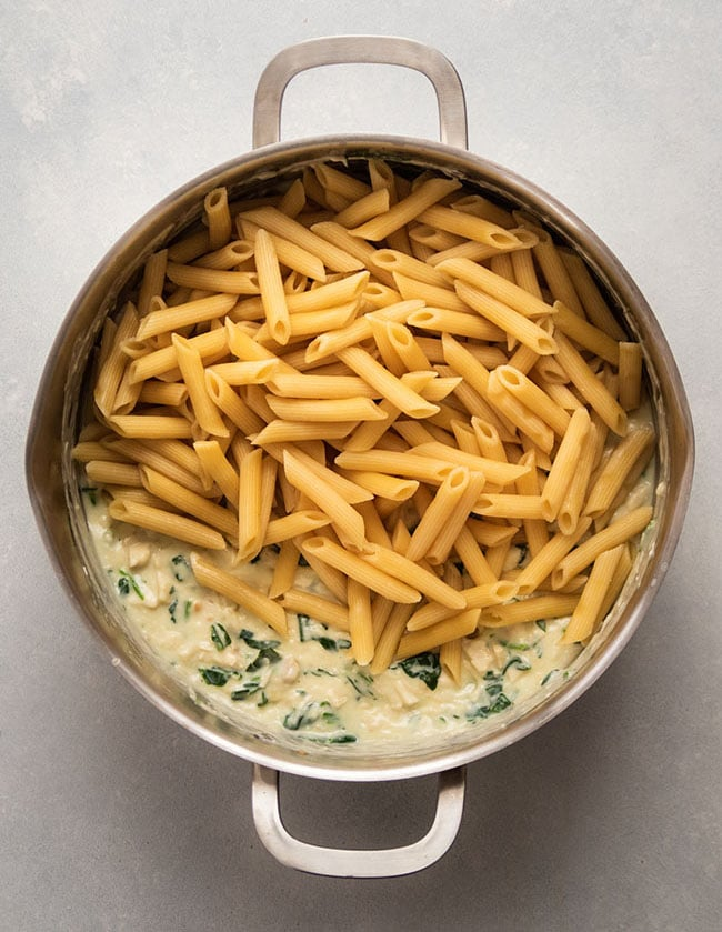 Adding cooked penne to parmesan sauce in a large pot.