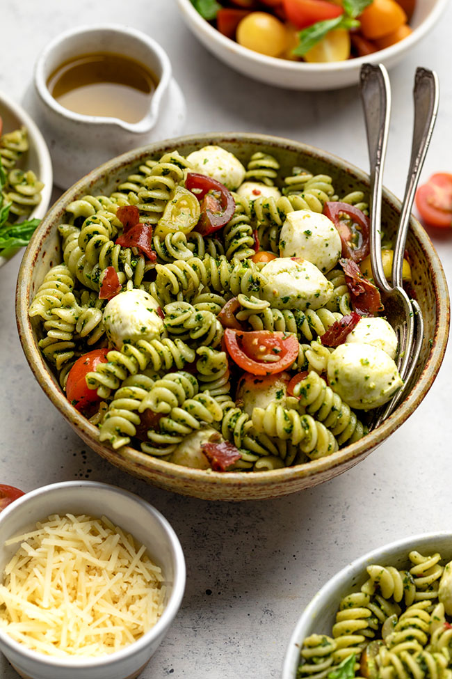 Pasta salad in a brown bowl next to a bowl of cherry tomatoes and extra parmesan cheese.