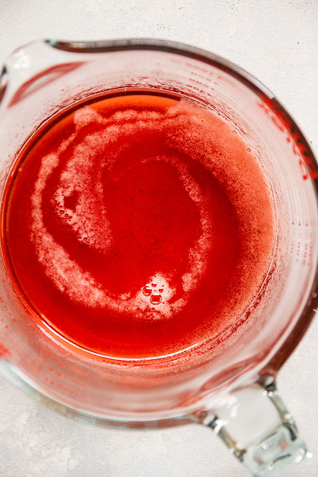 Looking into a glass measuring cup filled with bright pink strawberry thyme simple syrup.
