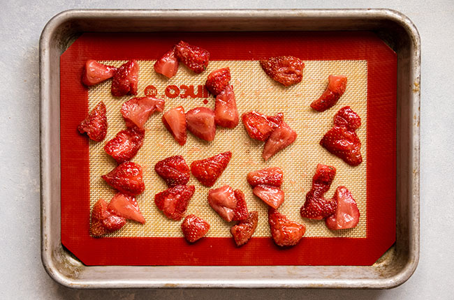 Cooked strawberries on a sheet pan lined with a nonstick baking mat, ready to freeze for smoothies.