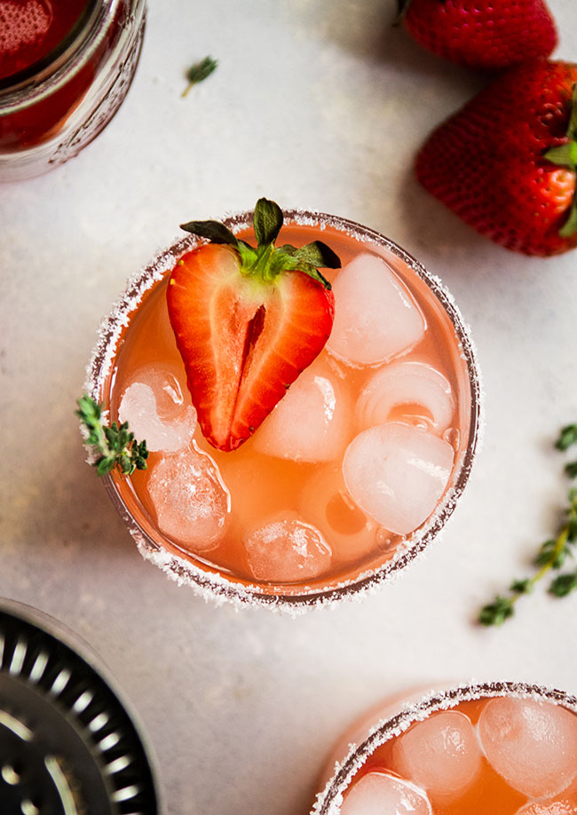 Overhead view of a strawberry cocktail in a glass with salt on the rim and half of a fresh strawberry on top.